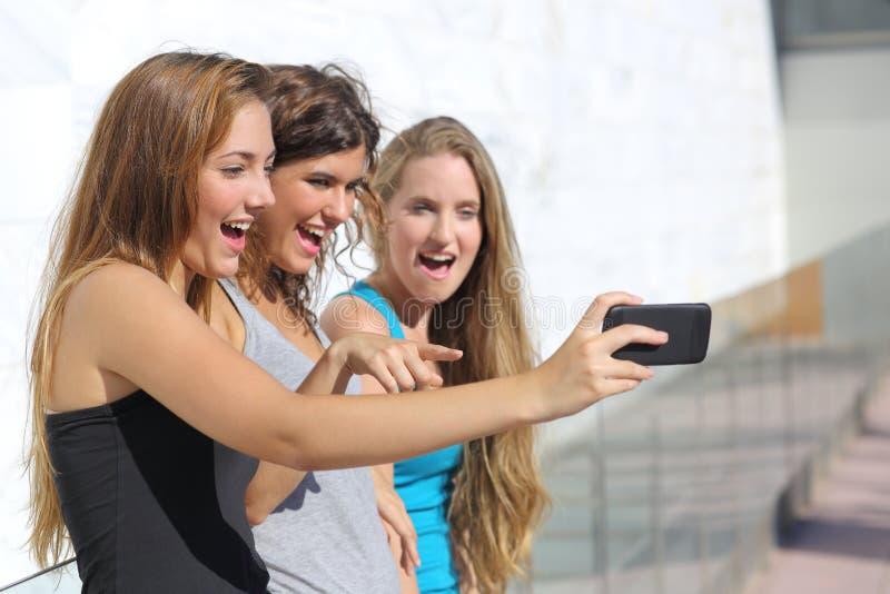 El grupo de tres muchachas del adolescente sorprendió la observación del teléfono elegante imagenes de archivo