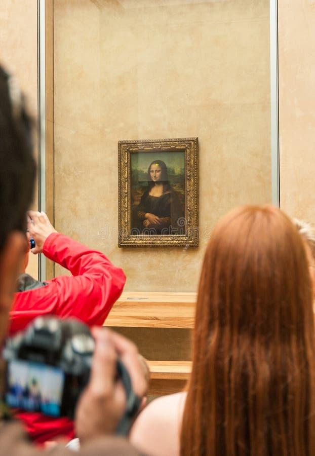 El grupo de turistas recolectó alrededor de Mona Lisa en el museo del Louvre foto de archivo
