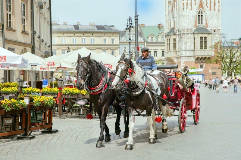 El grupo de turistas tiene excurtion en el carro de los caballos en la parte histórica de Kraków imágenes de archivo libres de regalías