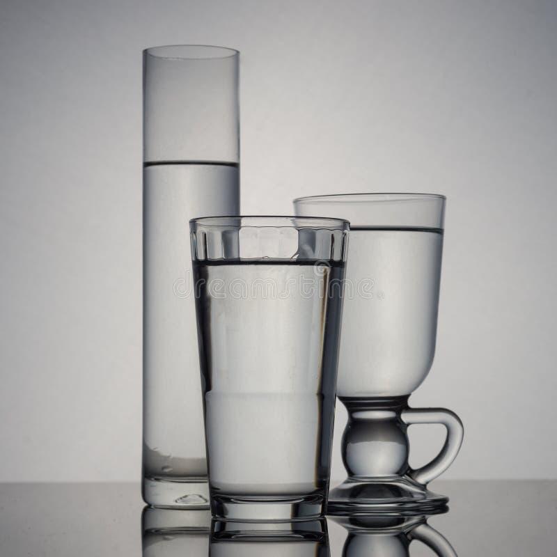 El grupo de vidrios llenó de agua en el fondo blanco fotos de archivo