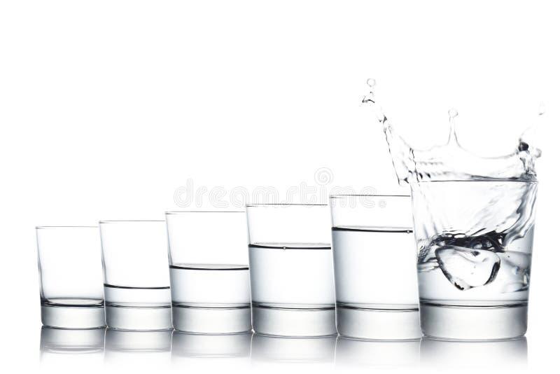 El grupo de vidrios llenó de diversos niveles de cubo del agua y de hielo que salpicaba adentro aislado en el fondo blanco, espac imagen de archivo