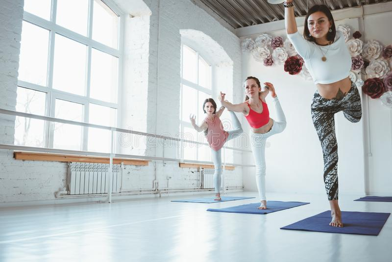 El grupo de yoga feliz joven de la práctica de la mujer plantea la clase interior entrenamiento del grupo imagenes de archivo