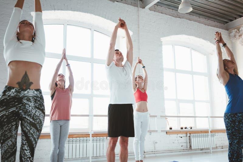 El grupo de yoga sana adulta de la práctica de la mujer plantea junto madrugada interior de la clase Concepto sano de la forma de foto de archivo