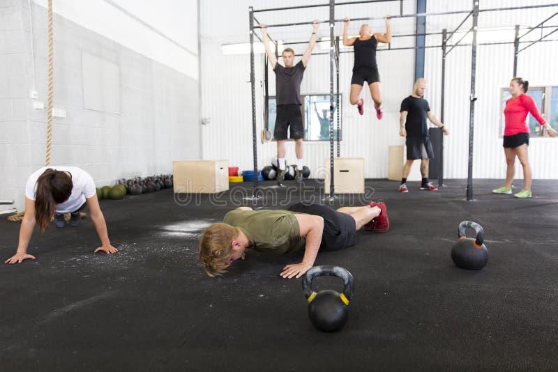 El grupo del entrenamiento hace ejercicios en el gimnasio de la aptitud imágenes de archivo libres de regalías