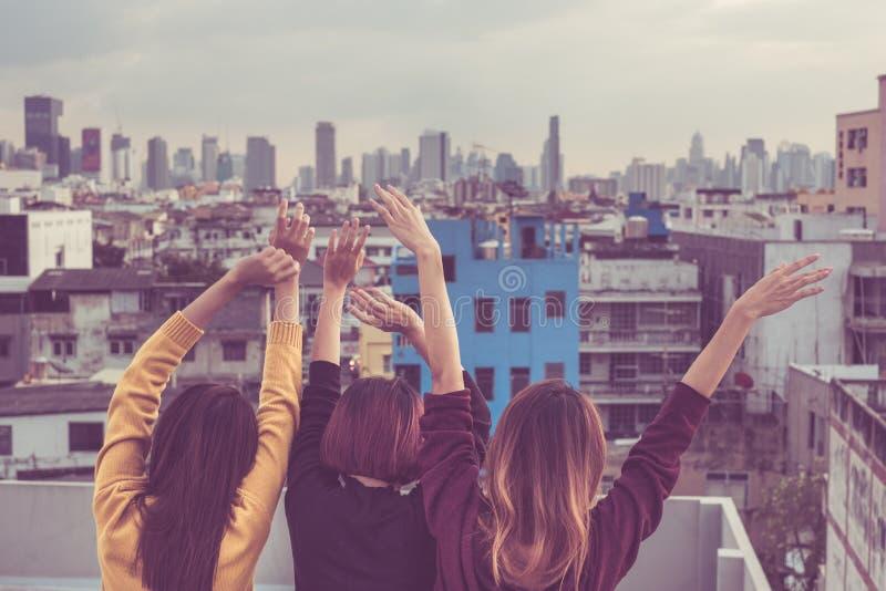 El grupo feliz de amigas de Asia goza y el brazo para arriba relaja actitud en foto de archivo libre de regalías