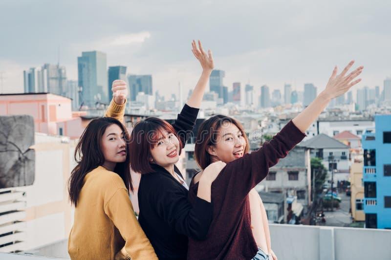 El grupo feliz de amigas de Asia goza y el brazo para arriba relaja actitud en imagen de archivo