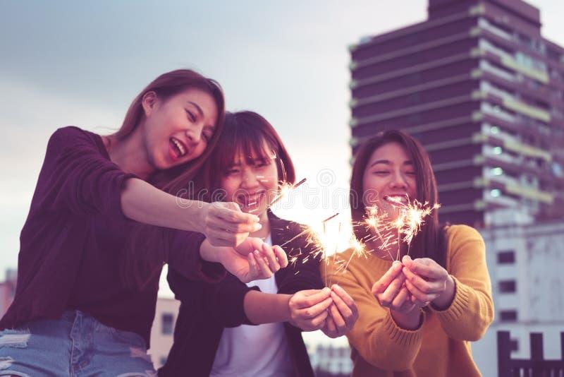 El grupo feliz de amigas de Asia goza y juega de la bengala en el tejado imagen de archivo