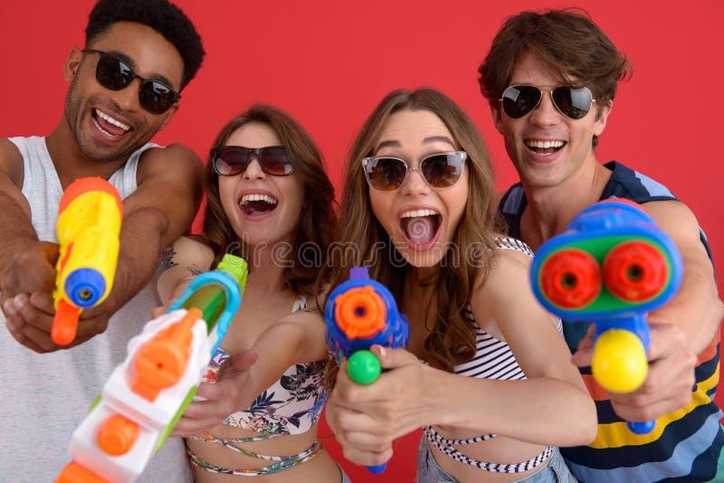 El grupo feliz joven de amigos con el juguete del agua dispara contra imágenes de archivo libres de regalías