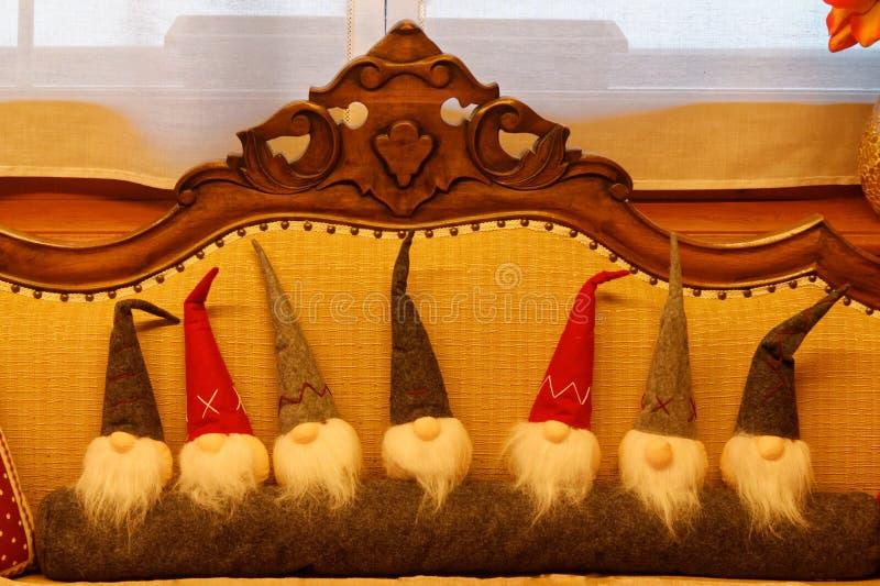 El grupo gnomos lindos suaves de Navidad de los duendes A del juguete de la Navidad de pequeños se sienta en un sofá Vista delant fotos de archivo