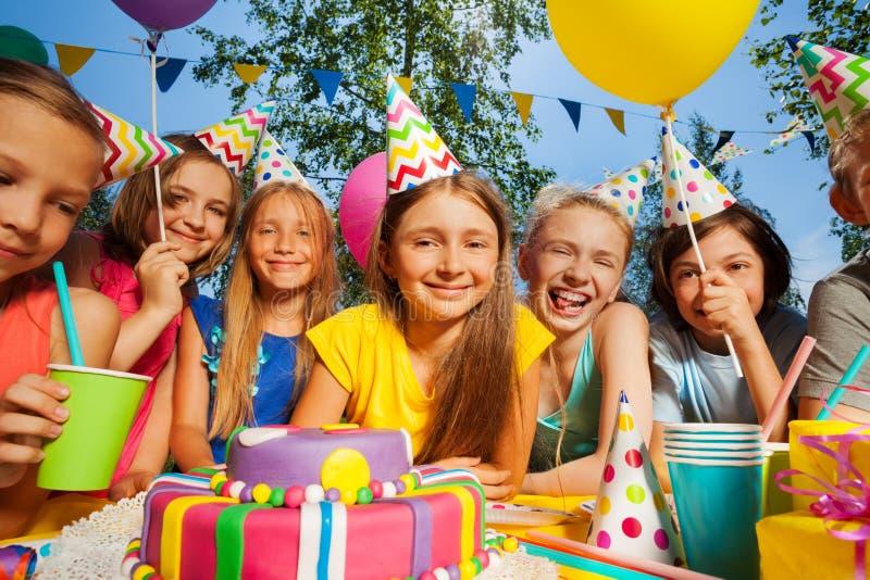 El grupo grande de sonrisa embroma alrededor de la torta de cumpleaños foto de archivo