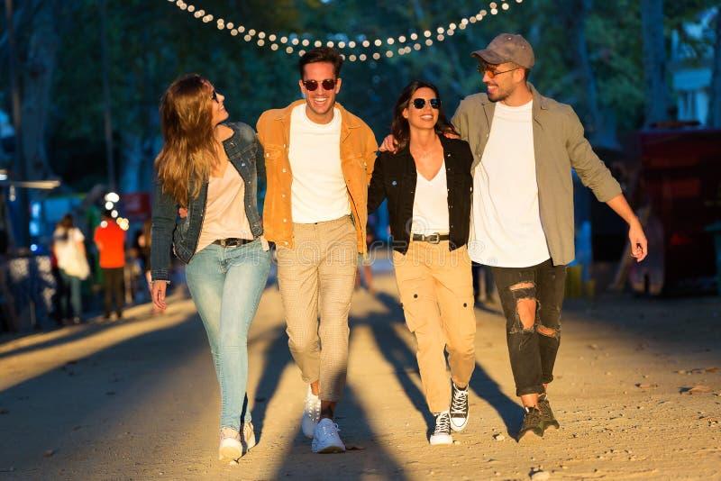 El grupo joven feliz y atractivo de amigos que disfrutan de tiempo adentro come el mercado en la calle fotos de archivo libres de regalías