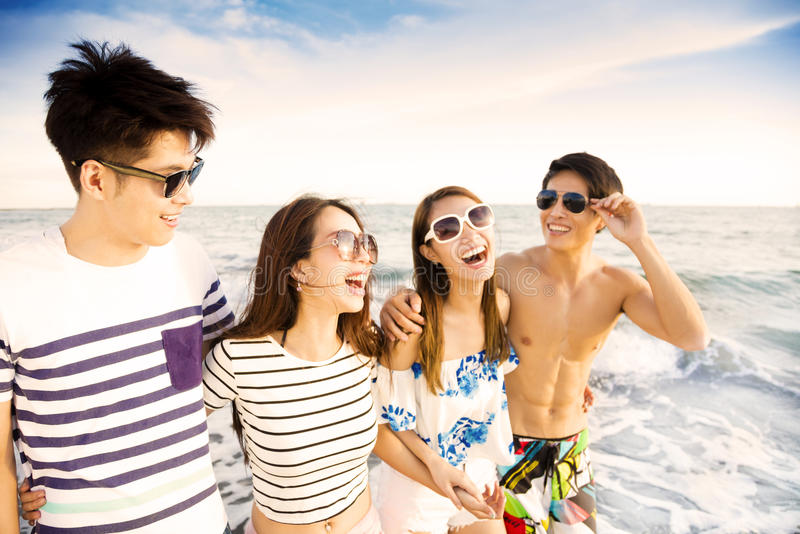 El grupo joven que camina en la playa disfruta de vacaciones de verano imágenes de archivo libres de regalías