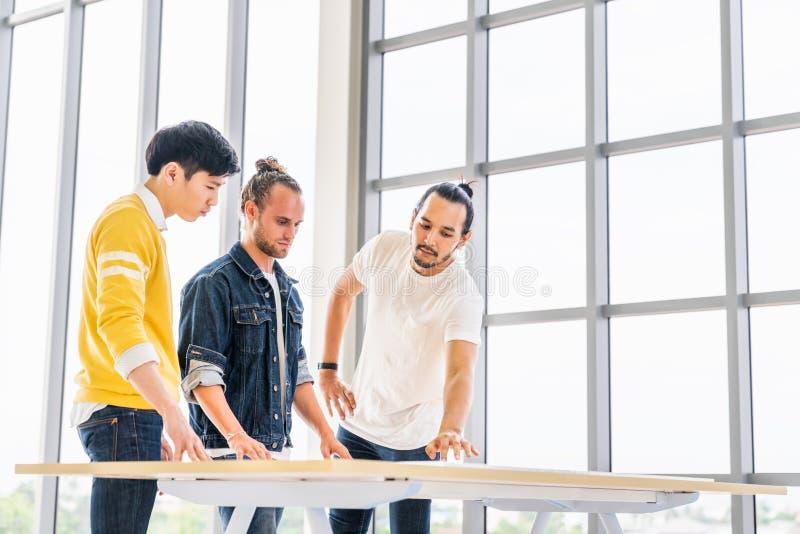 El grupo multiétnico de reunirse de tres hombres discute plan del proyecto del intercambio de ideas junto, oficina moderna con el foto de archivo libre de regalías