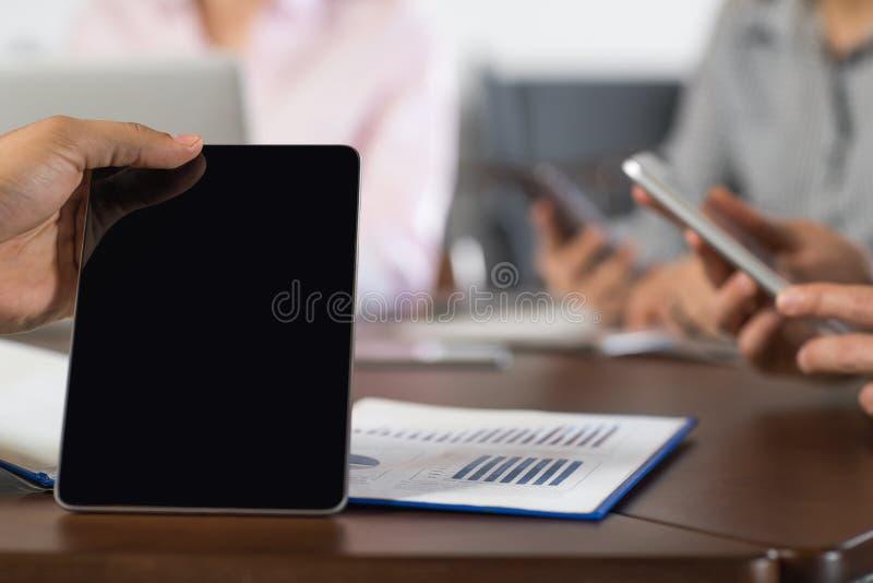 El grupo negro en blanco de los empresarios de la tableta de la mano en el centro de Coworking usando la célula Smart llama por t foto de archivo libre de regalías