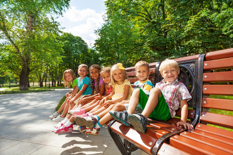 El grupo o los niños se basa sobre banco en parque imagen de archivo libre de regalías