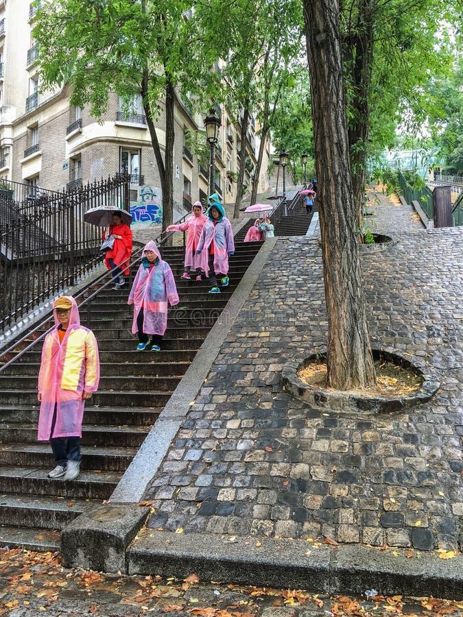 El grupo turístico en impermeables coloridos desciende las escaleras al aire libre cerca de Montmartre funicular fotos de archivo libres de regalías