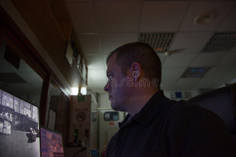 El guardia de seguridad masculino en lugar de trabajo mira el ligth bajo del monitor imagenes de archivo