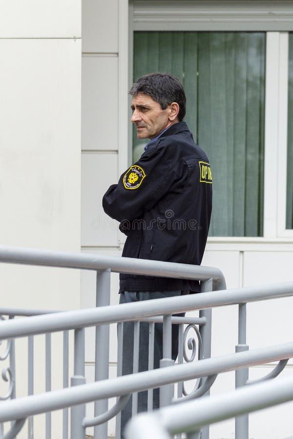 El guardia de seguridad masculino en uniforme negro cruzó sus brazos fotos de archivo libres de regalías