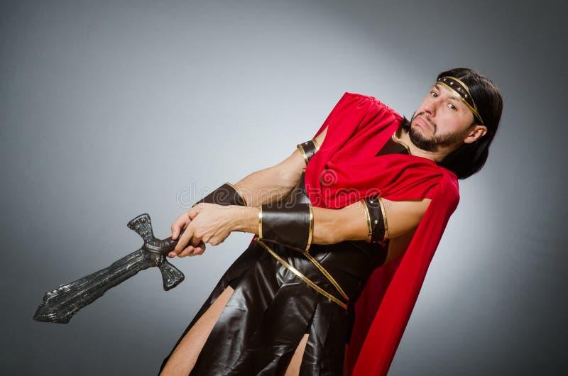 El guerrero romano con la espada contra fondo imagen de archivo