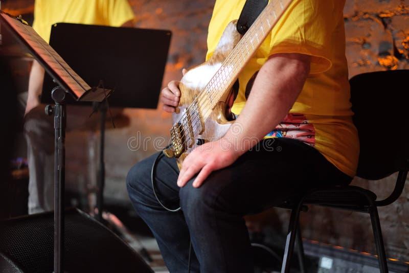 El guitarrista bajo durante la interrupción del concierto imágenes de archivo libres de regalías