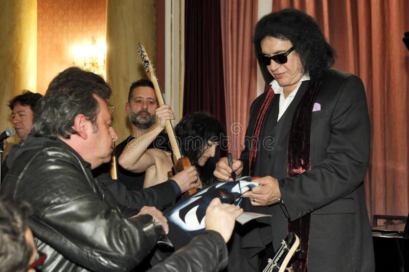 El guitarrista y el vocalista de una banda de rock besan a Gene Simmons foto de archivo