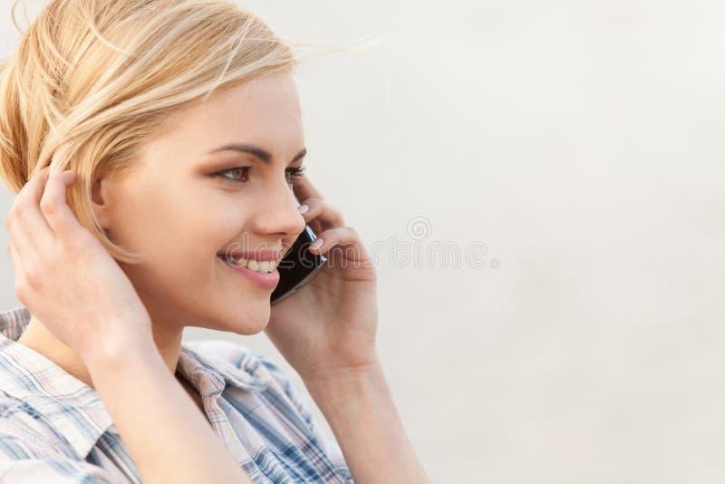 El hablar bastante rubio en el teléfono móvil y sonrisa imagen de archivo