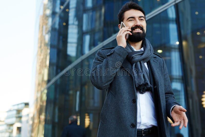 El hablar con el socio comercial en Smartphone foto de archivo