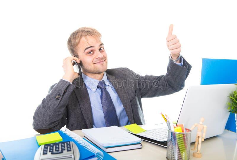 El hablar confiado sonriente del hombre de negocios feliz joven en el teléfono móvil en el escritorio del ordenador de oficina imagen de archivo libre de regalías
