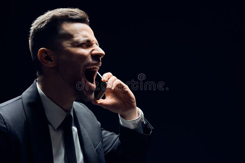 El hablar de griterío del hombre en el teléfono móvil con el espacio de la copia aislado en fondo oscuro foto de archivo libre de regalías