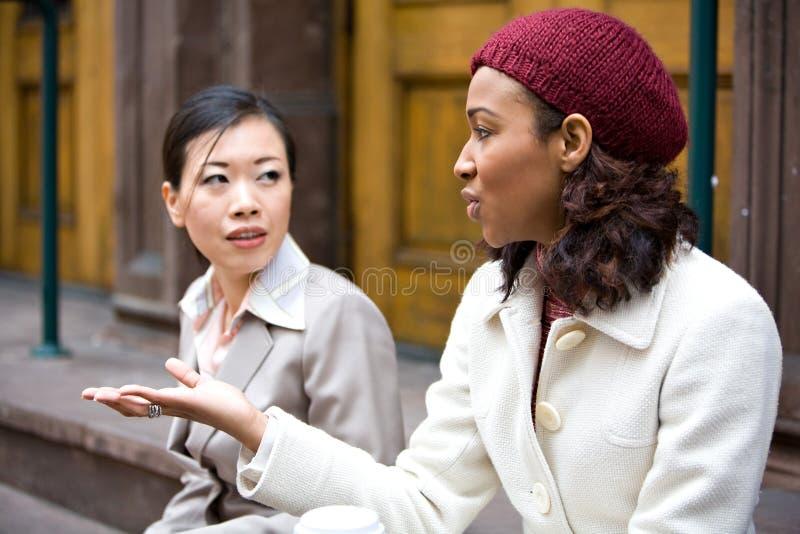 El hablar de las mujeres de negocios fotos de archivo