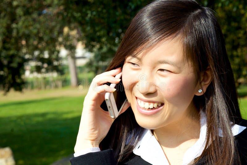 El hablar de relajación asiático feliz de la mujer de negocios en el teléfono en primer extremo sonriente del parque fotos de archivo libres de regalías