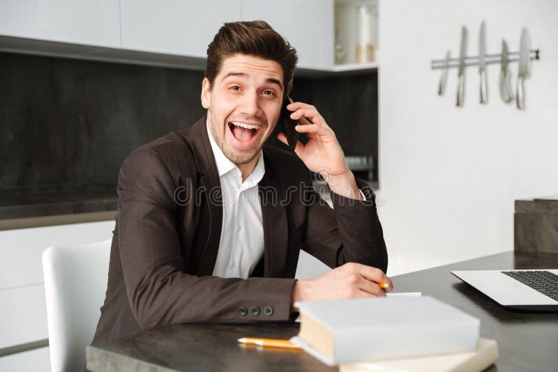 El hablar de trabajo chocado del hombre de negocios joven por el teléfono móvil fotos de archivo libres de regalías