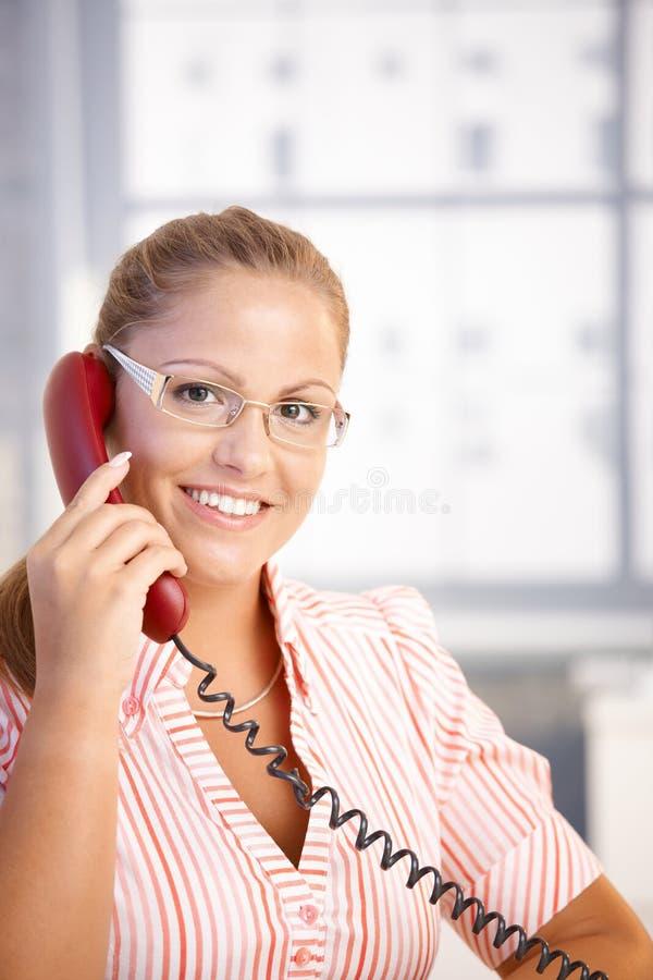 El hablar de trabajo del recepcionista bonito en el teléfono imagenes de archivo