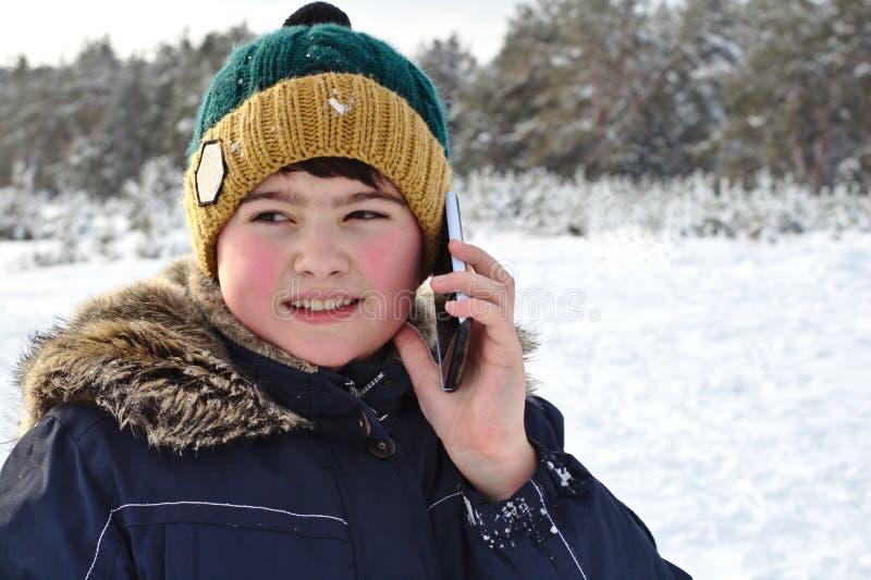 el hablar en el muchacho del teléfono en un sombrero hecho punto con una capilla del bubón y de la piel en un paseo del invierno fotos de archivo libres de regalías