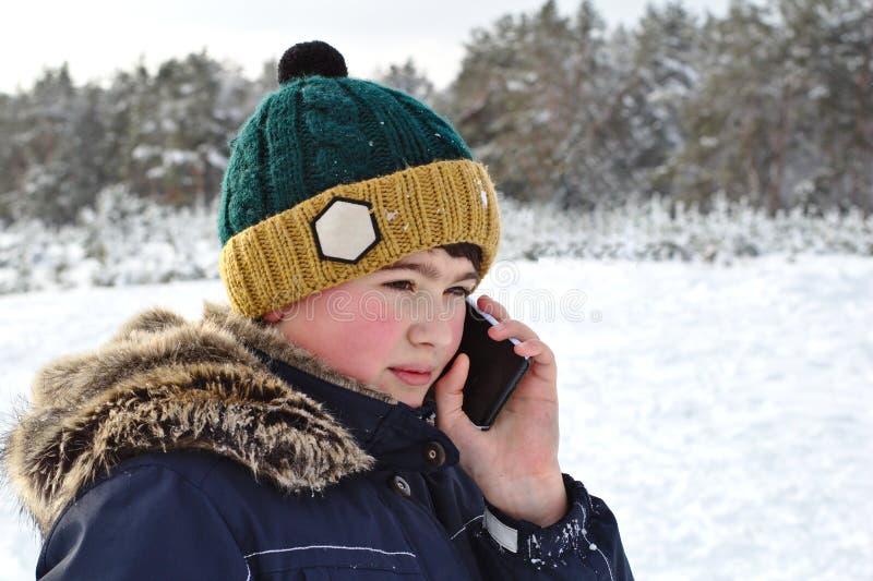 el hablar en el muchacho del teléfono en un sombrero hecho punto con una capilla del bubón y de la piel en un paseo del invierno imágenes de archivo libres de regalías