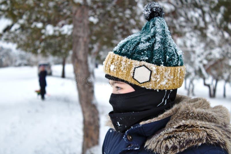 El hablar en el muchacho del tel?fono en un sombrero hecho punto con un bub?n y un pasamonta?as en un paseo del invierno foto de archivo libre de regalías
