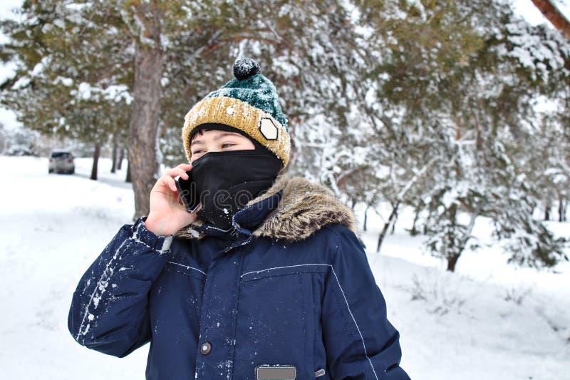 El hablar en el muchacho del tel?fono en un sombrero hecho punto con un bub?n y un pasamonta?as en un paseo del invierno imágenes de archivo libres de regalías
