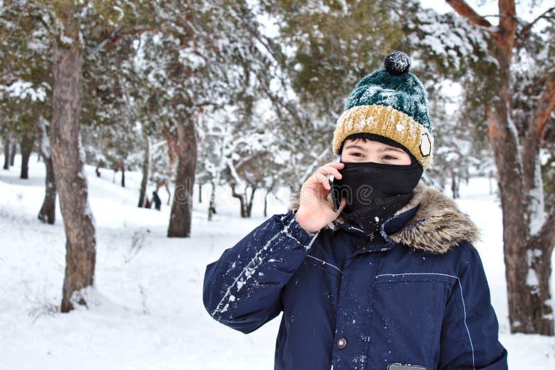 El hablar en el muchacho del tel?fono en un sombrero hecho punto con un bub?n y un pasamonta?as en un paseo del invierno fotografía de archivo