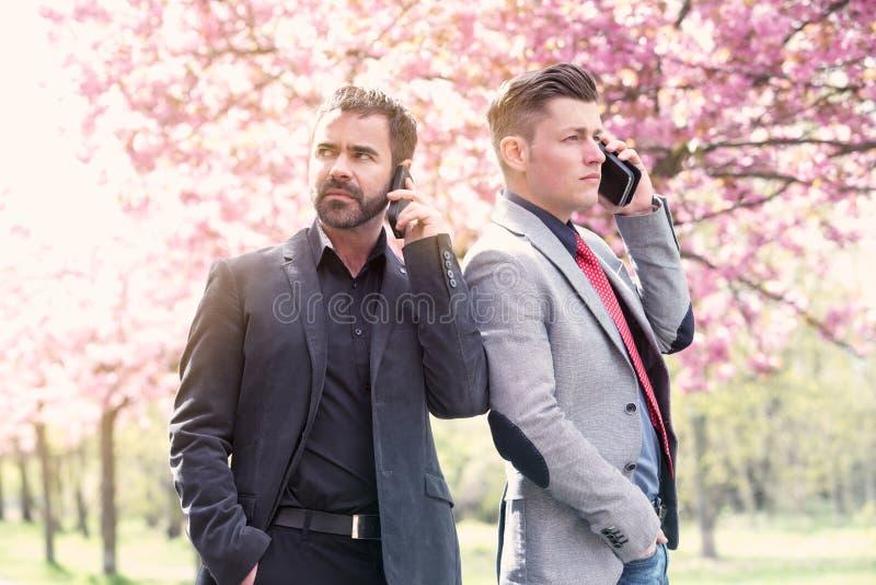 El hablar exterior de dos hombres de negocios en el teléfono fotos de archivo libres de regalías