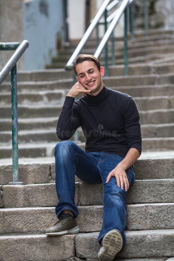 El hablar feliz joven de la imitación del individuo en un teléfono celular que se sienta en los pasos al aire libre foto de archivo libre de regalías