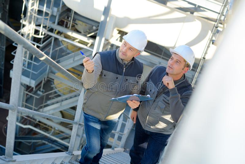 El hablar industrial masculino de los trabajadores del mantenimiento de la fábrica imagen de archivo