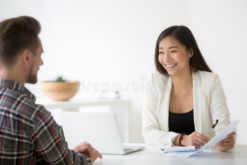 El hablar sonriente de la hora del asiático amistoso con el candidato en la entrevista de trabajo imágenes de archivo libres de regalías