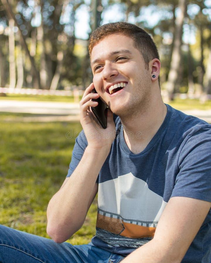 El hablar sonriente del adolescente en el teléfono móvil fotografía de archivo libre de regalías