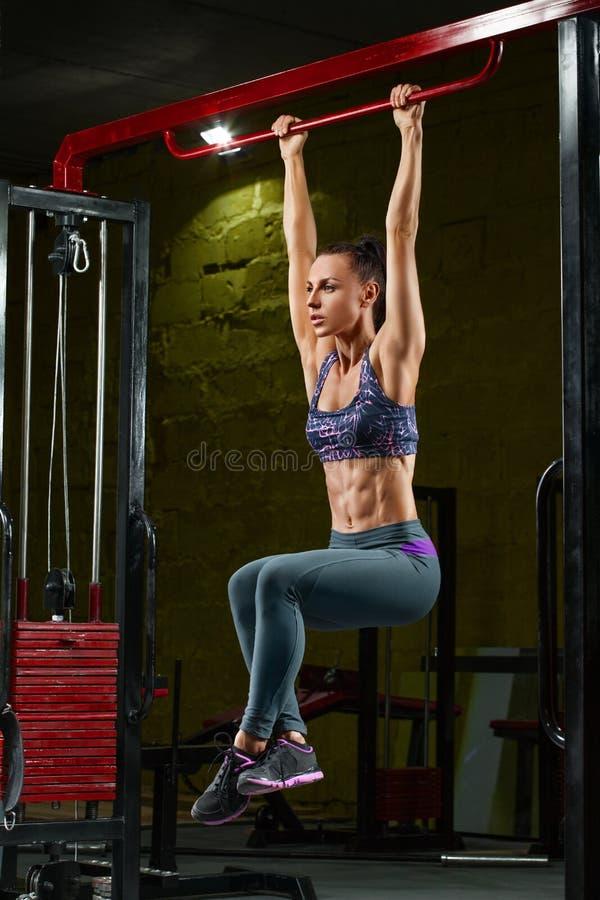 El hacer atractivo de la muchacha de la aptitud levanta en barra horizontal en gimnasio Mujer muscular, ABS, abdominal formada fotografía de archivo libre de regalías