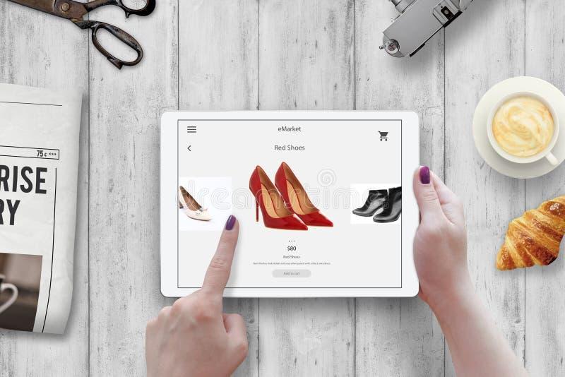 El hacer compras con la tableta Zapatos rojos de la compra de la mujer en mercado en línea fotografía de archivo