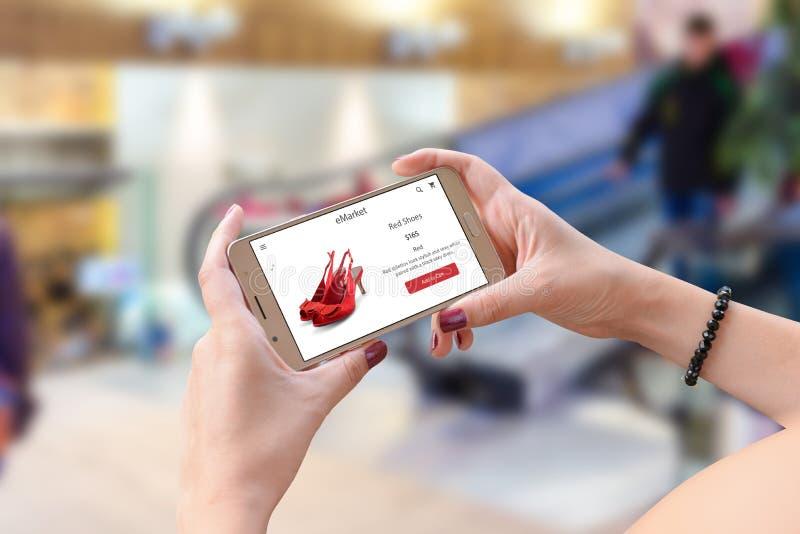 El hacer compras con el teléfono móvil Mujer que sostiene el teléfono elegante en la posición horizontal fotografía de archivo