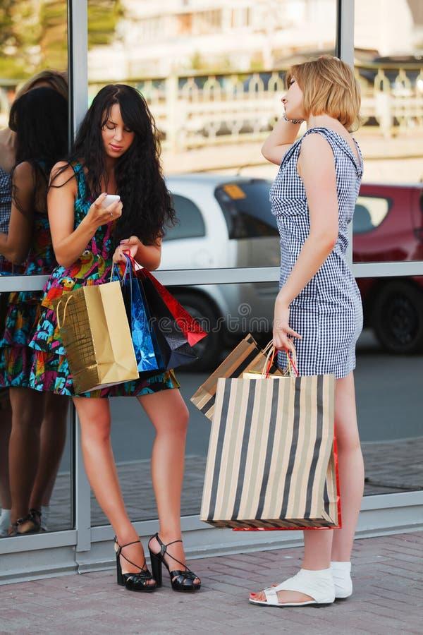 El hacer compras de dos mujeres jovenes imágenes de archivo libres de regalías