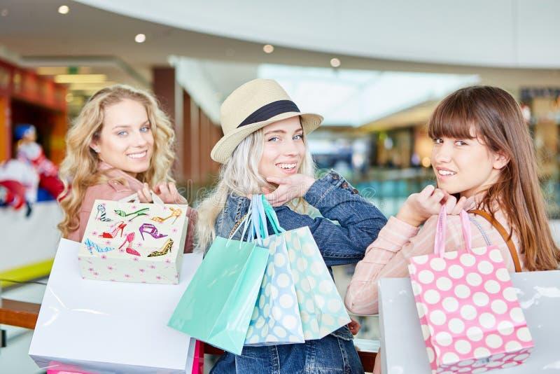 El hacer compras de tres mujeres jovenes imagenes de archivo