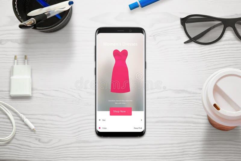 El hacer compras en línea con un teléfono móvil La mujer elige tamaño y el color del vestido con la tienda app fotografía de archivo