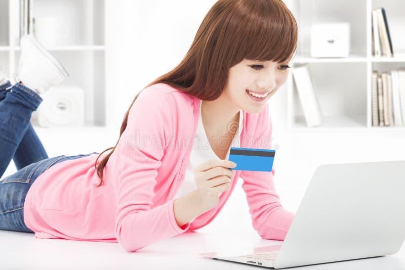 El hacer compras en línea de la mujer joven en casa con la tarjeta de crédito foto de archivo libre de regalías